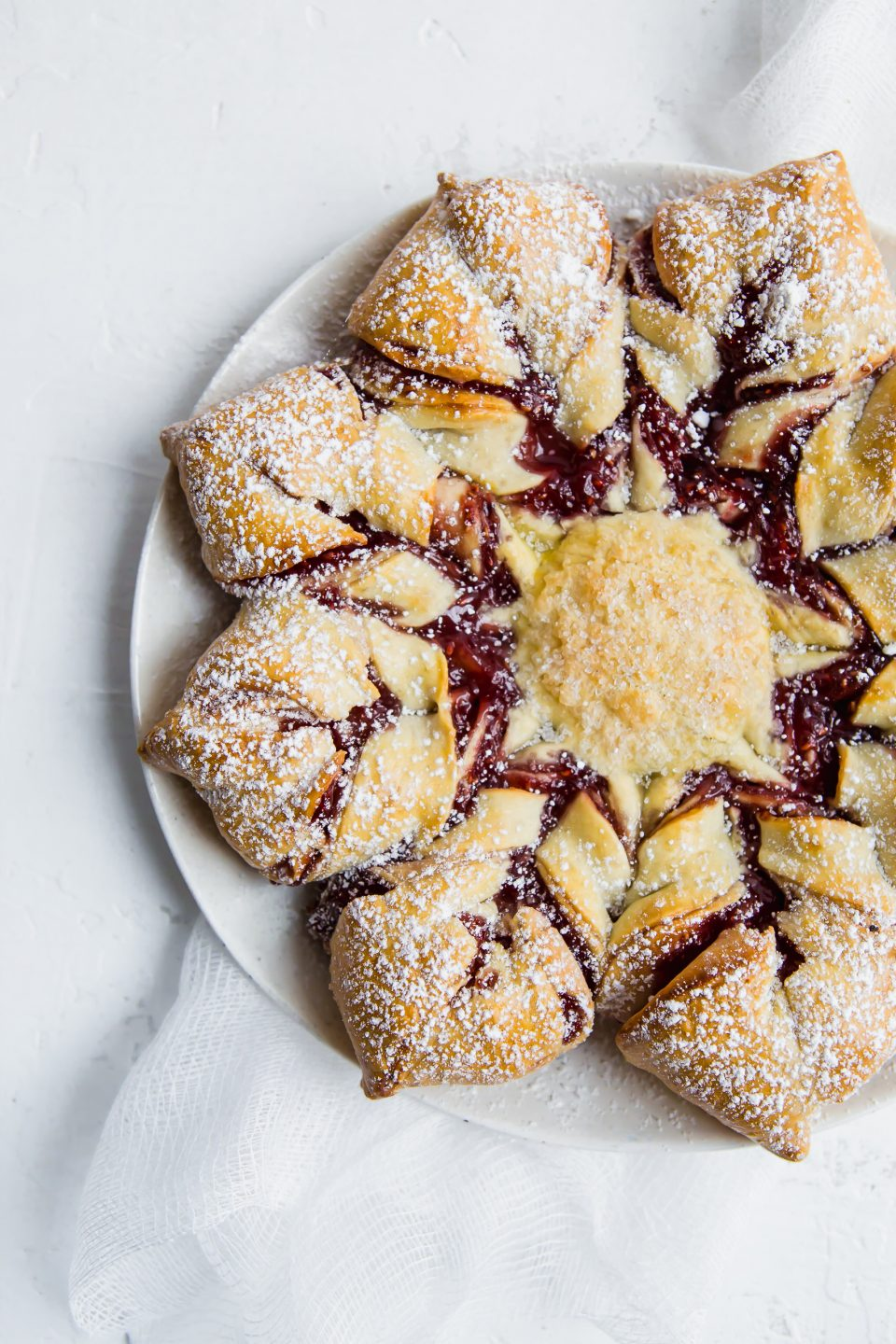 Overhead photograph of a raspberry filled pastry shaped like a star.