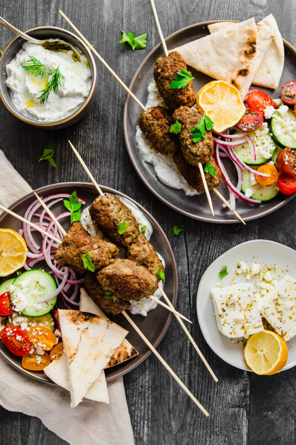 An overhead shot of two dark gray plates on a dark background. There are gluten-free greek lamb meatballs on wooden skewers on each plate. Around the skewers are chopped tomatoes, cucumbers, feta cheese, pita bread and lemons.