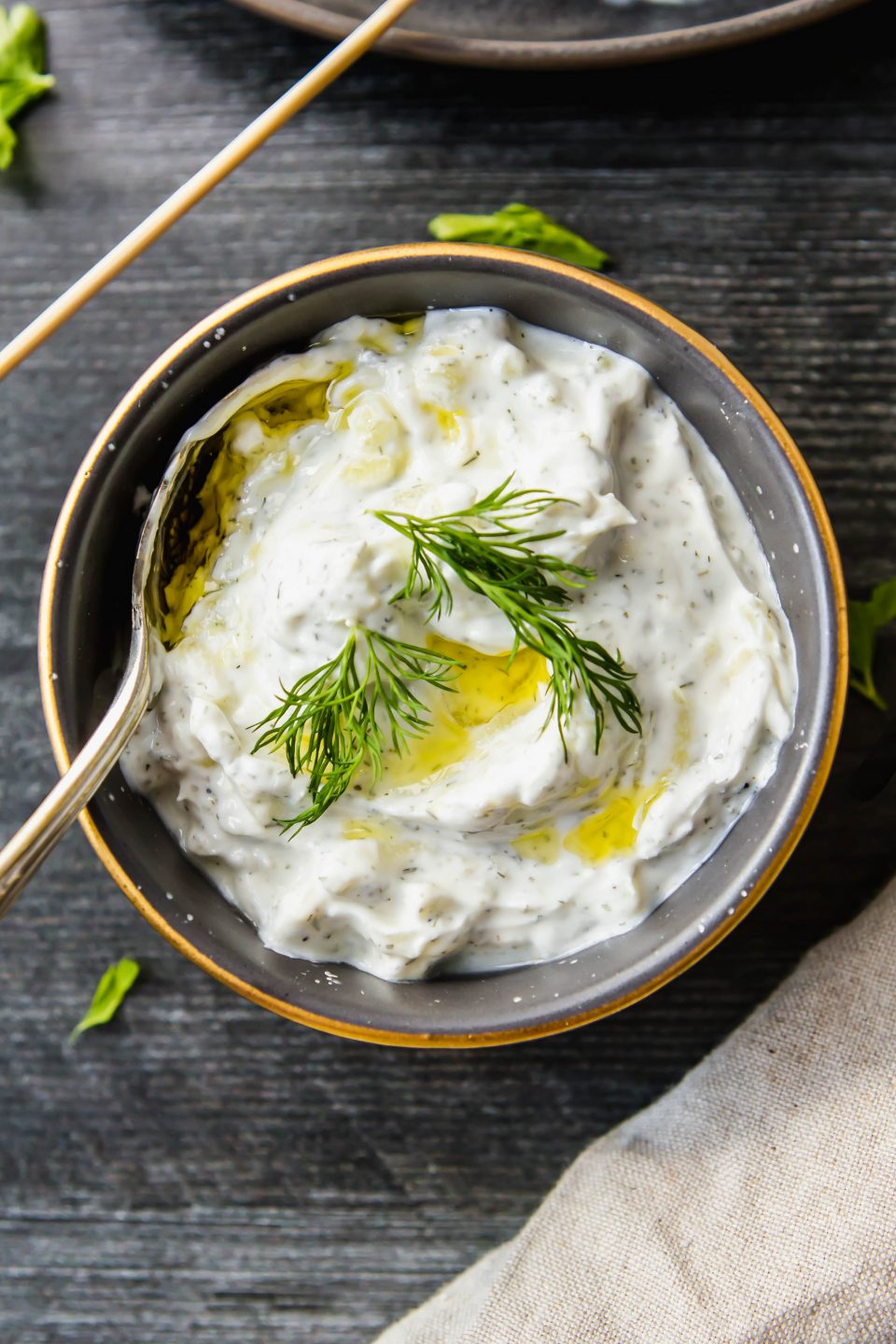 An overhead photo of a bowl of tzatziki sauce made with greek yogurt, lemon, dill and garlic. It is swirled with olive oil and topped with fresh dill.