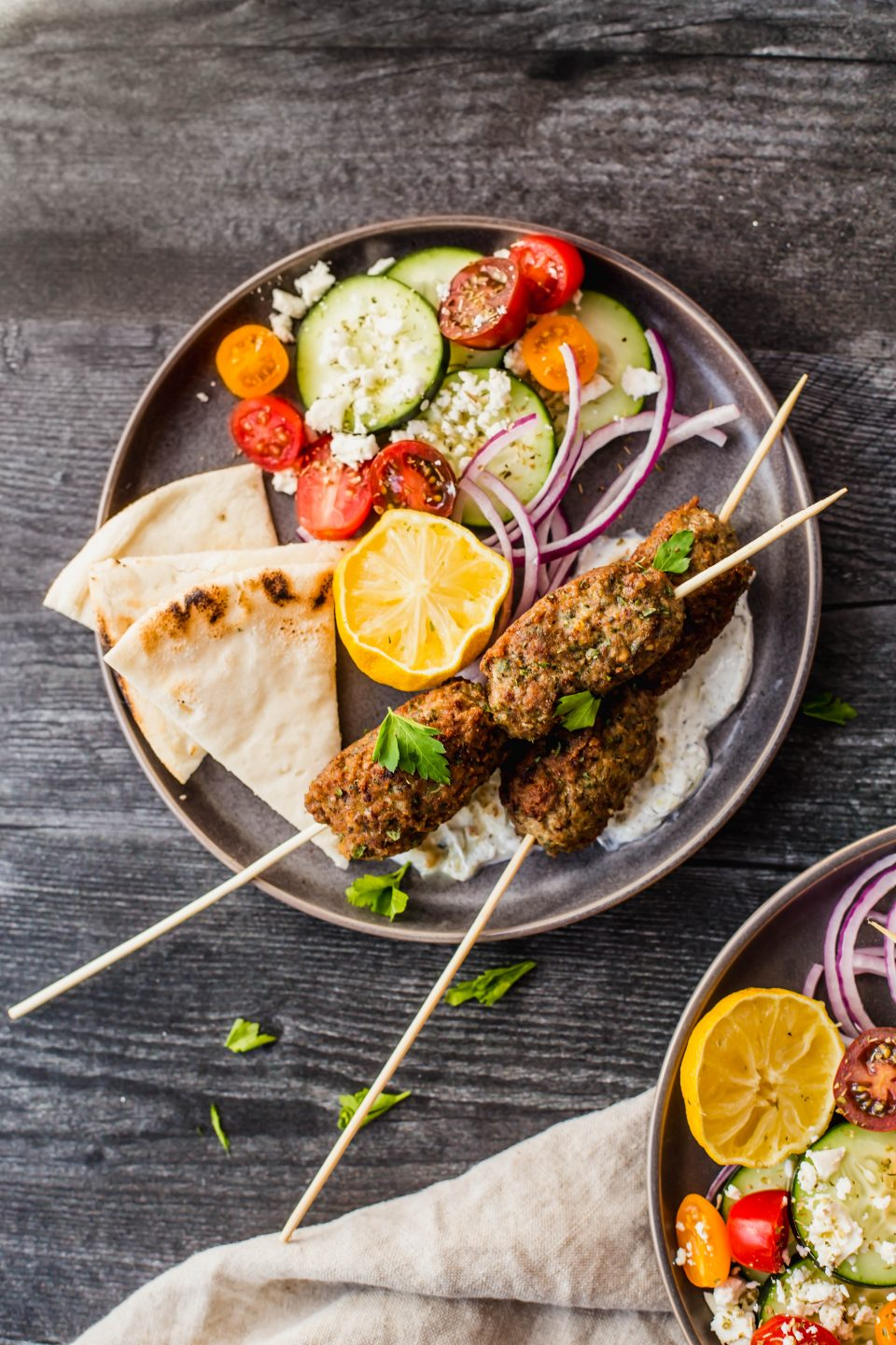 An overhead shot of a dark gray plate on a dark background. There are gluten-free greek lamb meatballs on wooden skewers on each plate. Around the skewers are chopped tomatoes, cucumbers, feta cheese, pita bread and lemons.