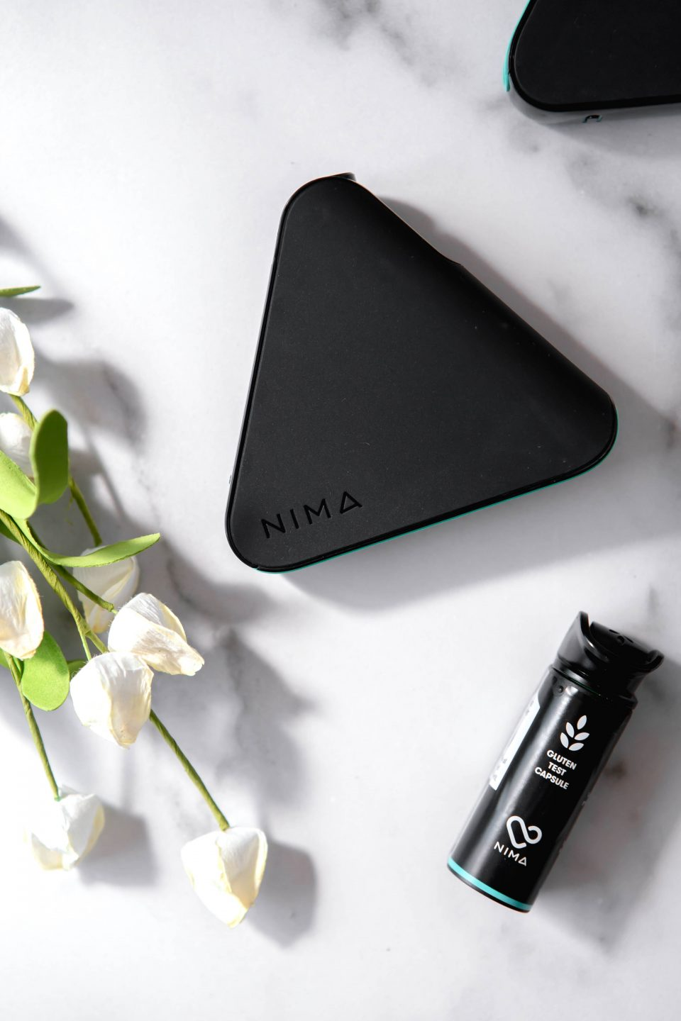 Nima Sensor with flowers and a gluten sensor capsule placed a marble backdrop.