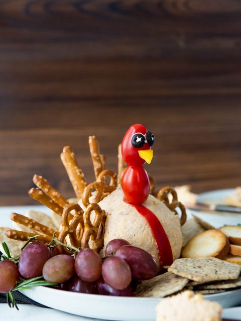 Cheeseball shaped to look like a turkey. Pretzel twists and sticks are placed in the back to look like turkey feathers. A few tomatoes on a toothpick make a turkey head. Plate shows crackers and grapes to dip in the cheese.