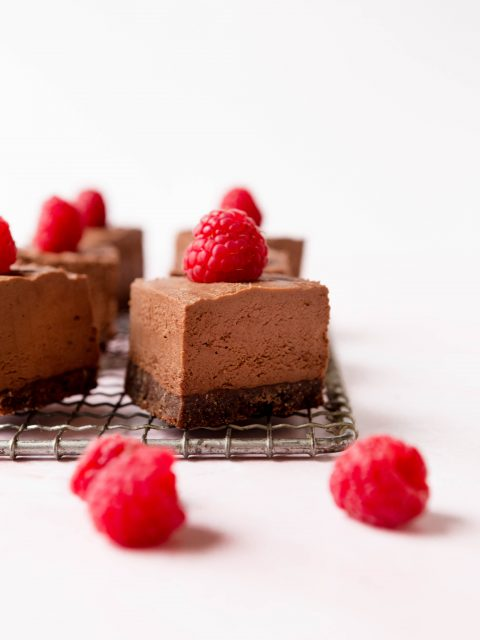 Straight on shot of chocolate cheesecake bars with a chocolate crust. Raspberries are places on top and scattered in the foreground.