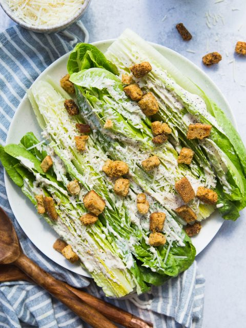 Overhead shot of hearts of romaine cut in half and smeared with caesar dressing. Some wooden spoons are placed overlapping in the bottom right.
