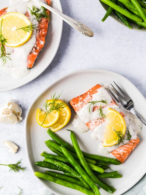 An overhead shot of salmon filets a plate dried with a cream sauce and topped with lemon slices and fresh dill.