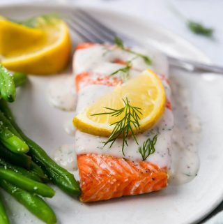 One piece of salmon drizzled with a cream sauce and topped with a lemon slice and dill. Green beans are on the side of the plate and lemon wedges are in the background.