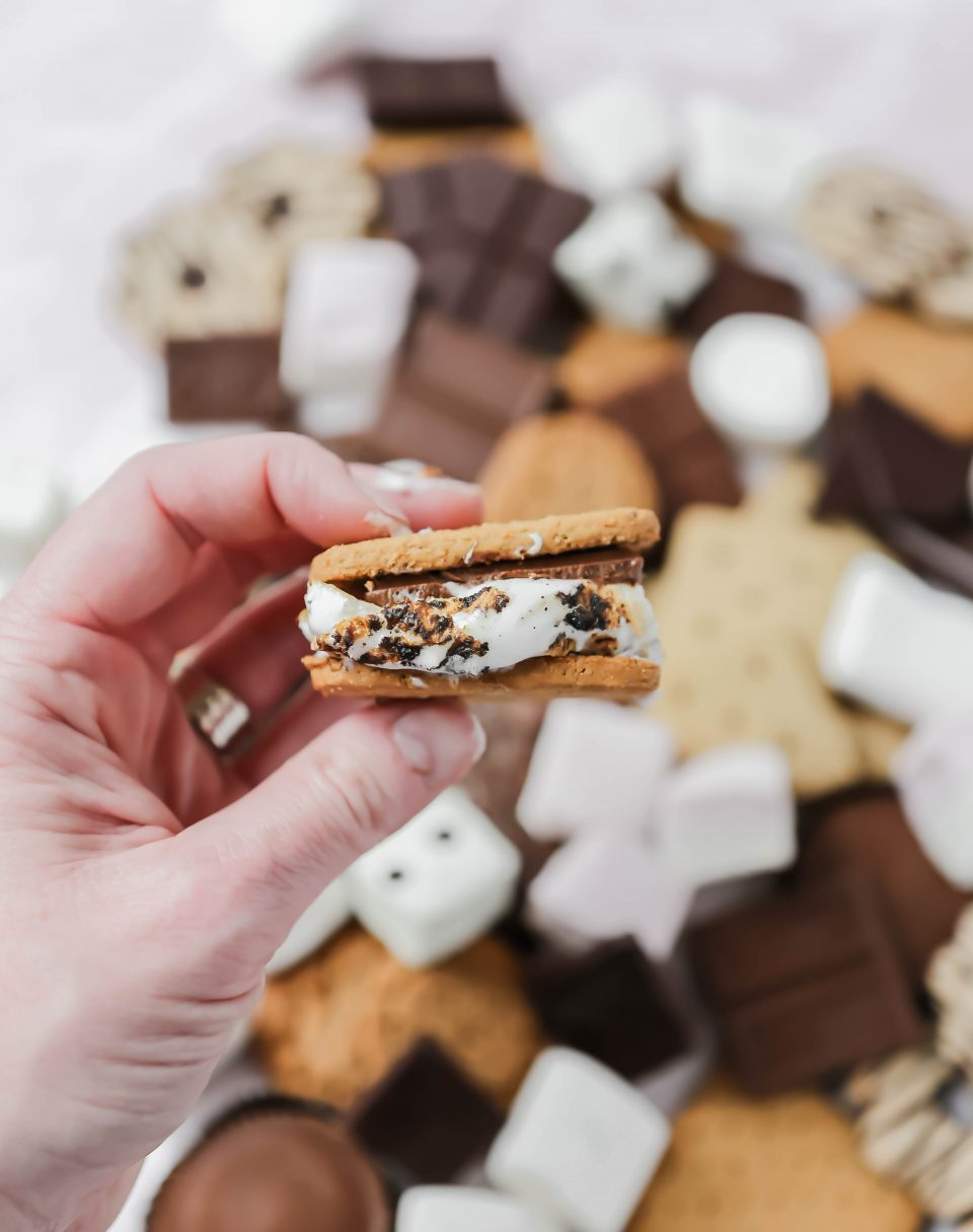 Photo of a hand holding a gluten-free s'more made with graham crackers, chocolate and toasted marshmallow.