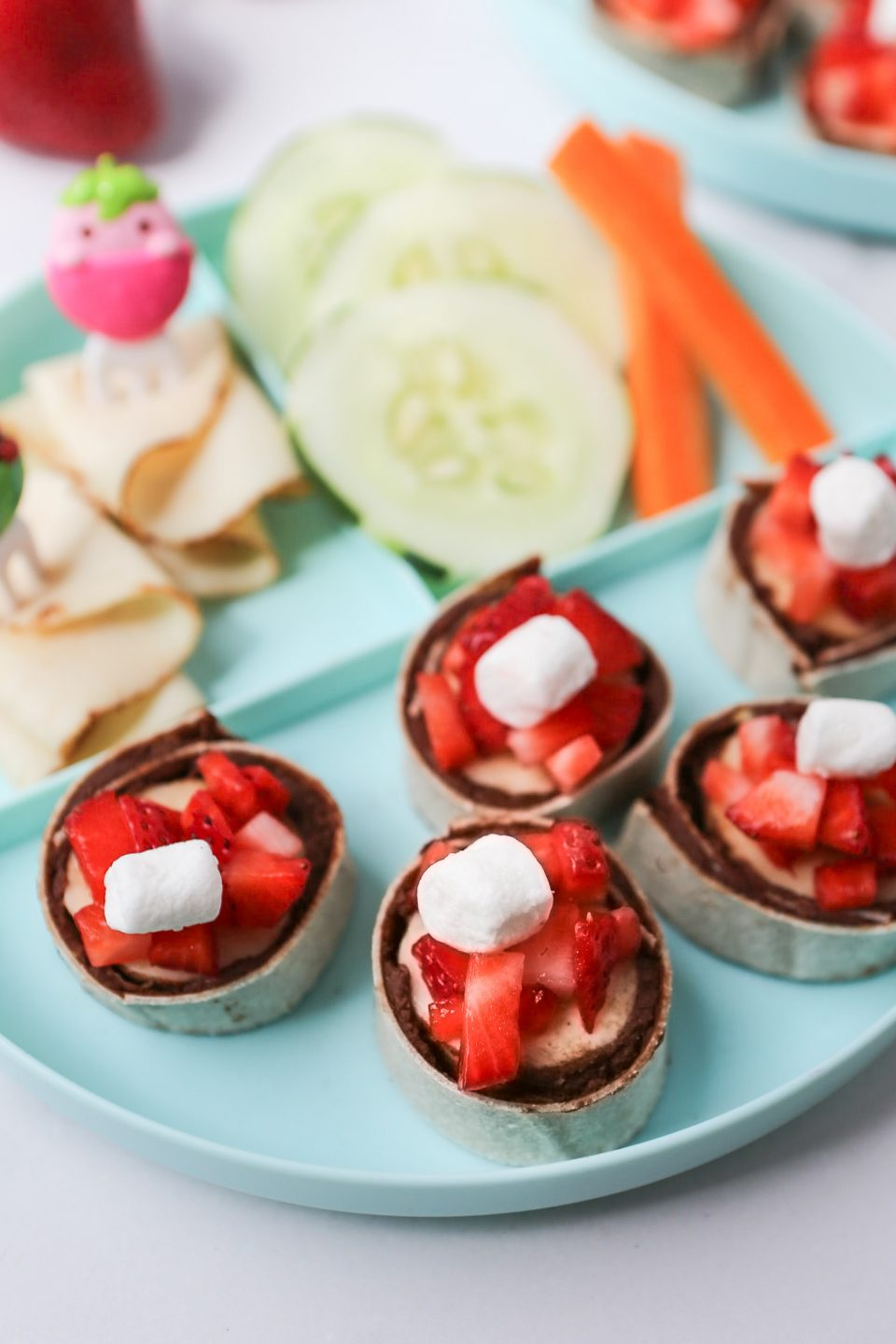 A 90 degree angle photo of banana/chocolate roll-ups with strawberries. Places on blue plates with veggies and turkey in the background.