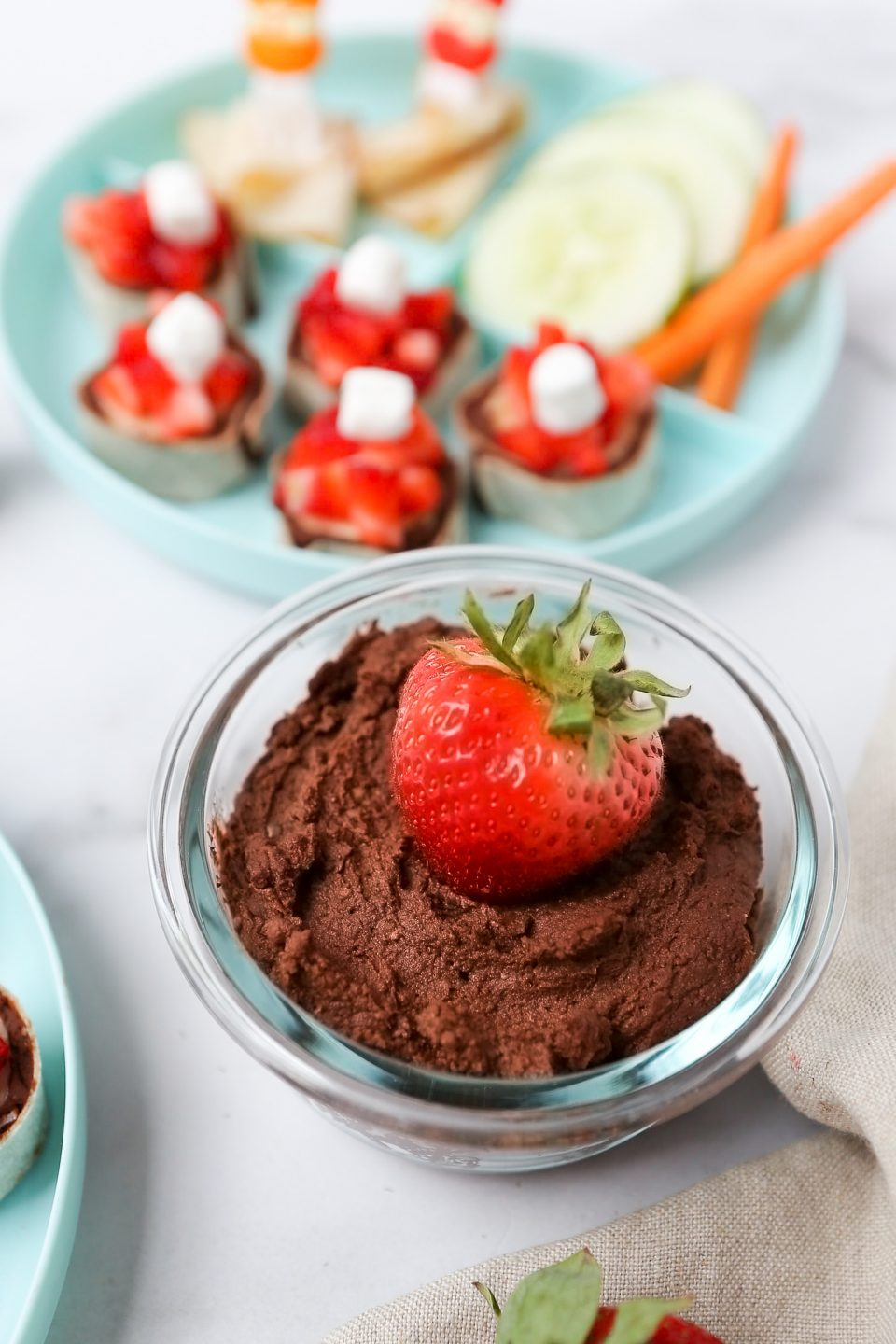 An overhead photos of homemade chocolate hummus in a small bowl with a strawberry placed in the middle. There is a kids plate with veggies and turkey slices the background.