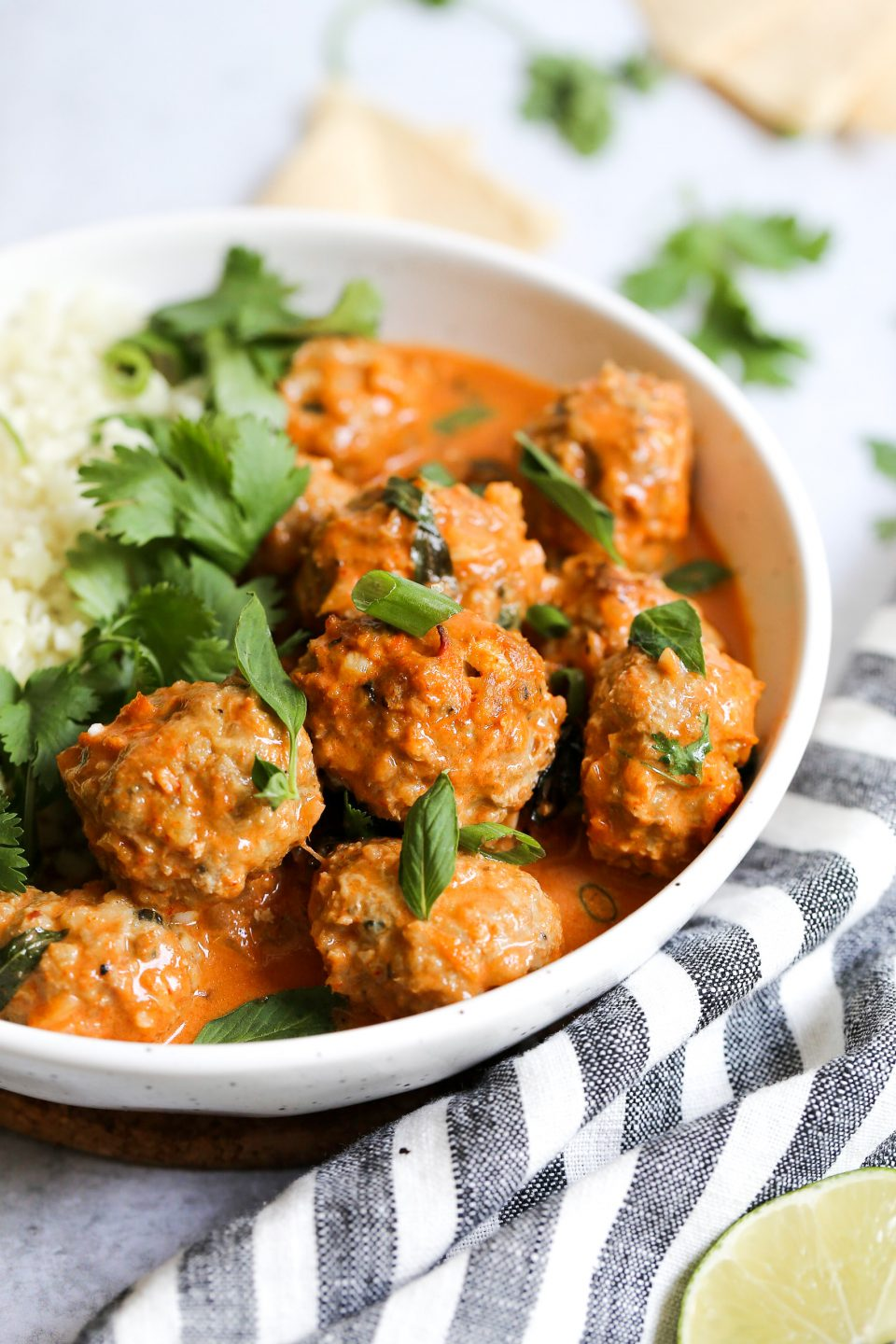 A 90 degree angle of thai coconut curry turkey meatballs placed in a bowl with cauliflower rice and garnished with big leaves of cilantro.