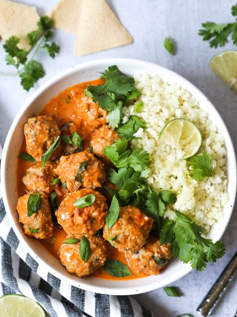 Overhead shot of a bowl of cauliflower rice with thai coconut curry meatballs. Cilantro, lime wedges, and green onions are scattered around..