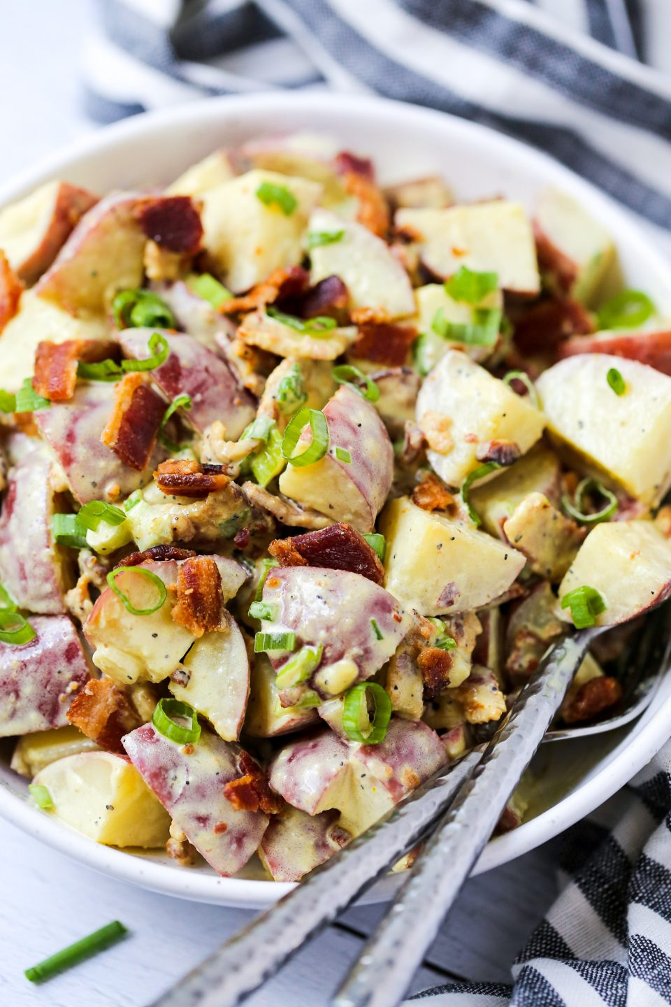Potato salad with a honey mustard dressing and topped with chives and bacon.