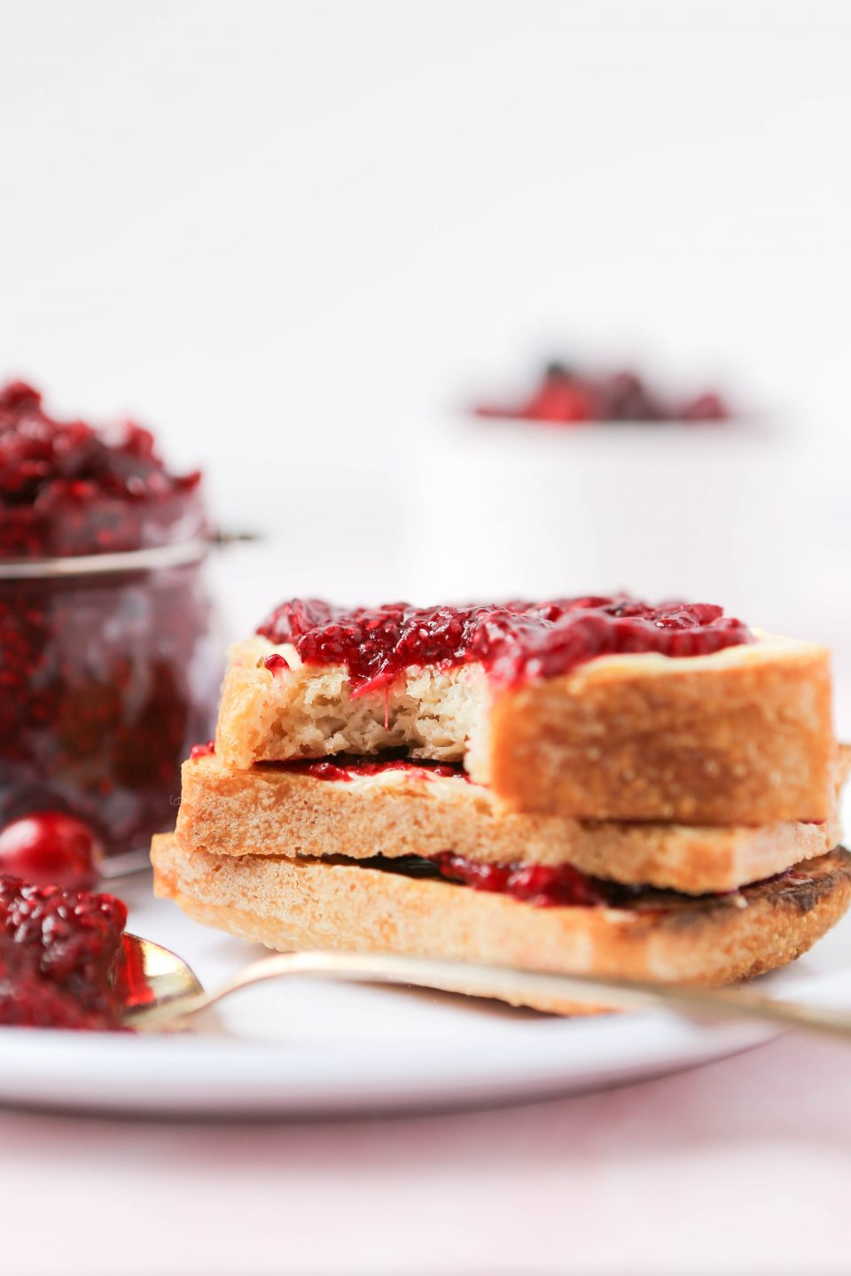 A plate of three pieces of gluten-free sourdough bread layered with butter and cranberry chia seed jam. There is a spoonful of the jam in the forefront and a bowl of cranberries in the background.