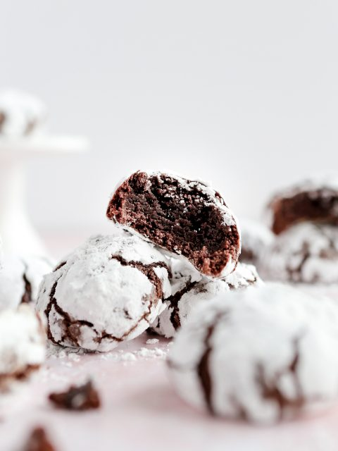 Photo of chocolate crinkle cookies sideways stacked on top of each other. There is a bite taken out of the cookie in focus. Dark chocolate cookies covered isn powdered sugar.