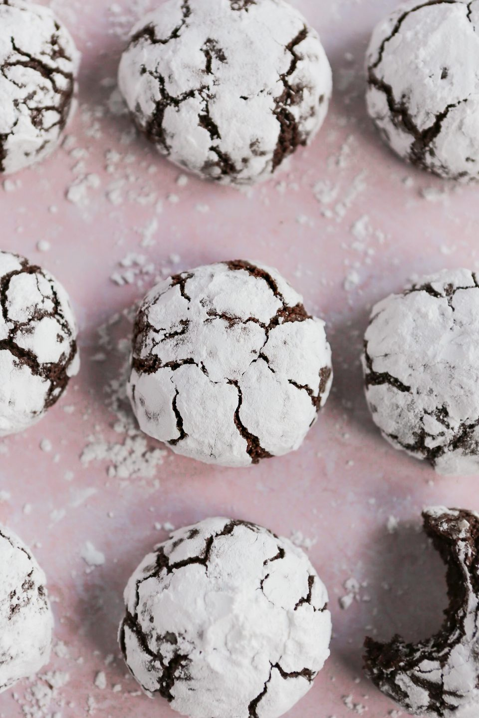 Overhead shot of chocolate crinkles cookies covered in powdered sugar. There are three rows of three cookies with powdered sugar scattered around the pink background the cookies are on.