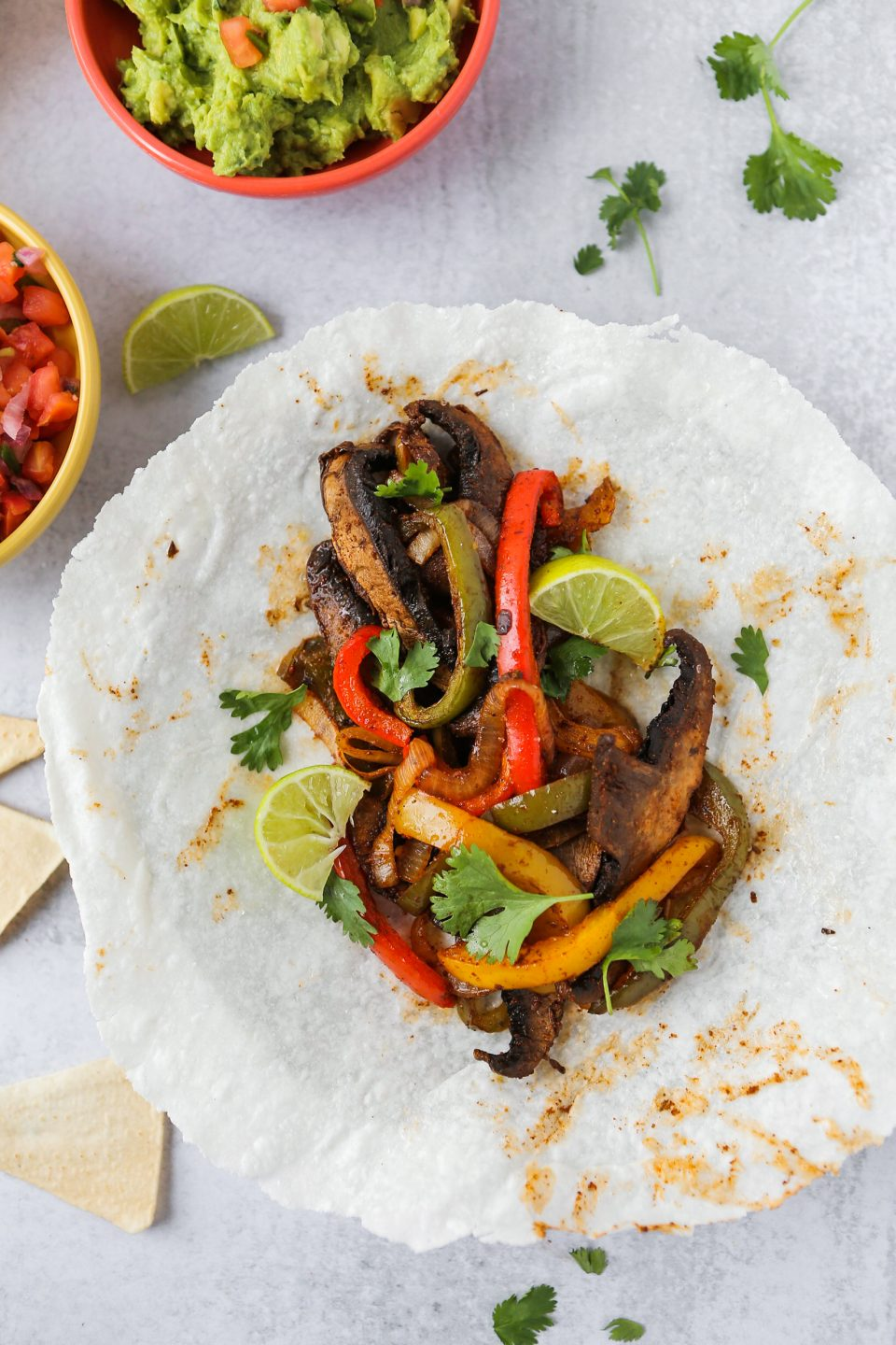 An overhead photo of portobello fajitas in a grain-free wrap by The Real Coconut. There are coconut tortilla chips and cilantro scattered about.