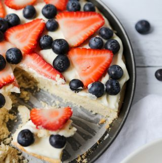 Overhead photo of a gluten-free fruit pizza. A slice of the round pizza is missing and you can see the layers of cookie, frosting, and fresh fruit.