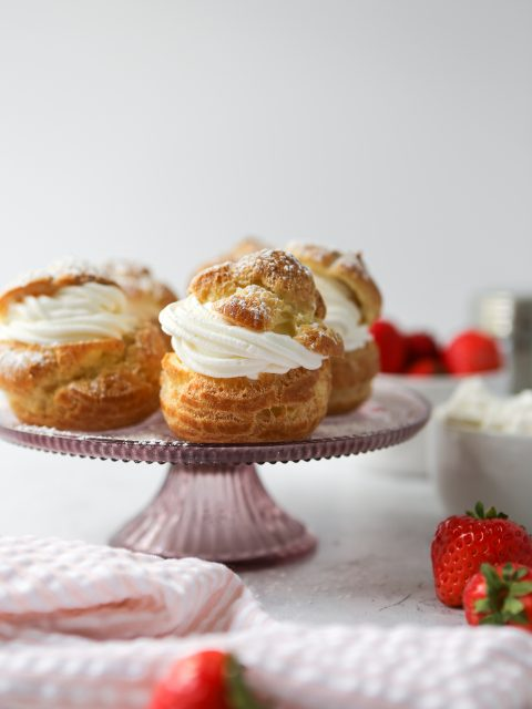 Gluten-free cream puff on a light pink cake pedestal. There are strawberries scattered throughout the photo.